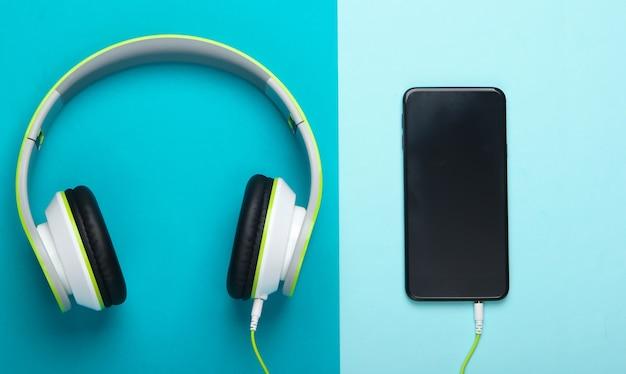 Stijlvolle bedrade stereohoofdtelefoon met smartphone op blauw oppervlak