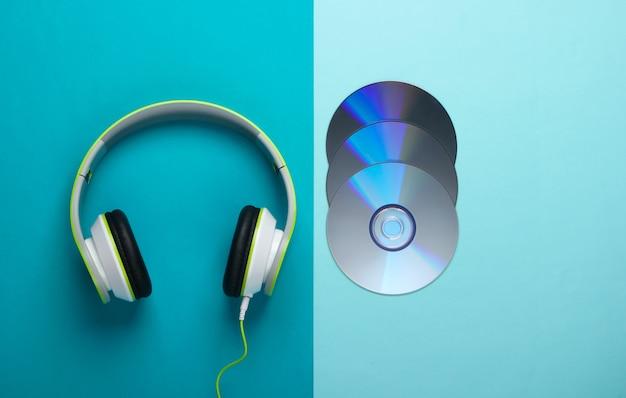 Stijlvolle bedrade stereohoofdtelefoons en cd-schijven op blauw oppervlak