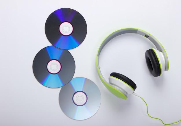Stijlvolle bedrade stereohoofdtelefoons en cd-schijven op wit oppervlak