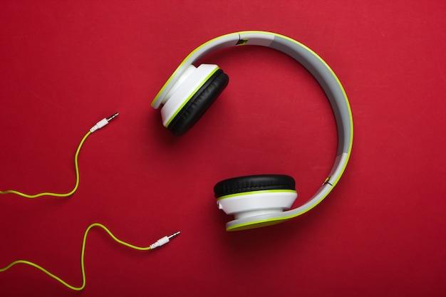 Stijlvolle bedrade stereohoofdtelefoons op rood oppervlak