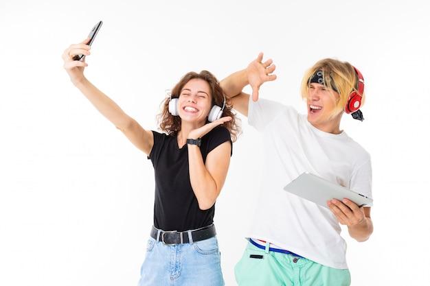 Stijlvolle blanke blonde man en jonge vrouw doen selfie en luisteren naar muziek geïsoleerd op een witte muur