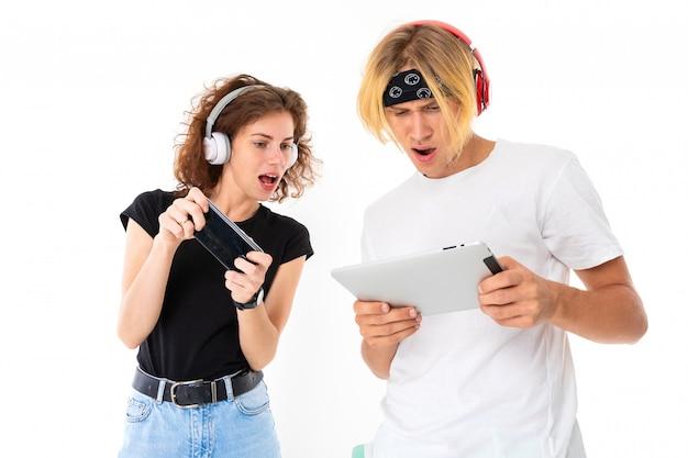 Stijlvolle blanke blonde man en jonge vrouw spelen telefoonspelletjes en luisteren naar muziek op een witte muur