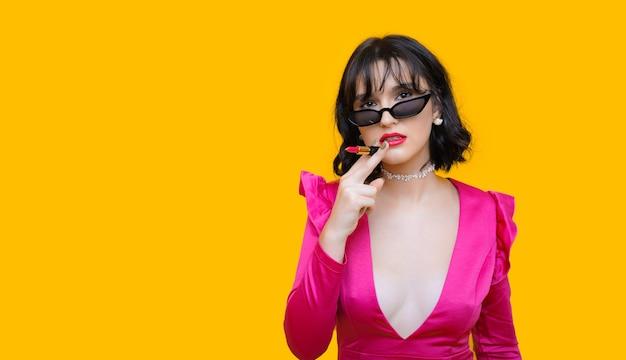 Stijlvolle blanke brunette dame houdt een lippenstift terwijl ze door een bril kijkt en poseren op een gele muur met vrije ruimte