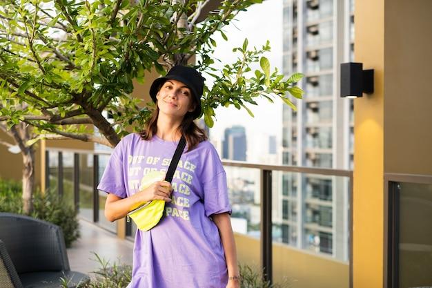 Stijlvolle blanke vrouw in trendy panama en neon heuptas op dak in bangkok.