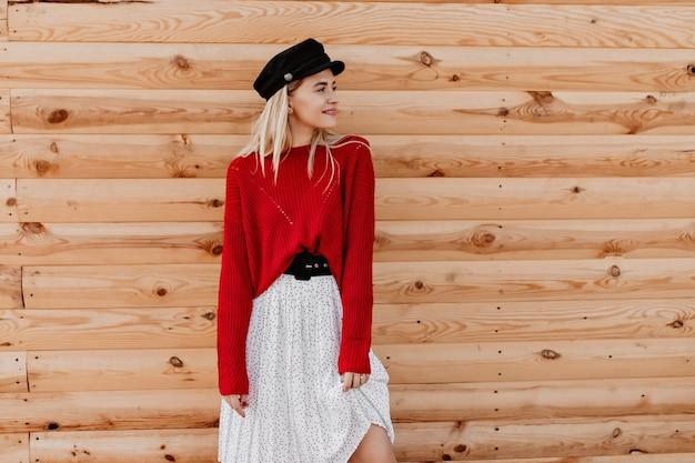 Stijlvolle blonde dragen zwarte riem en witte jurk poseren op de houten muur. mooie jonge vrouw die aantrekkelijk dichtbij het huis kijkt.