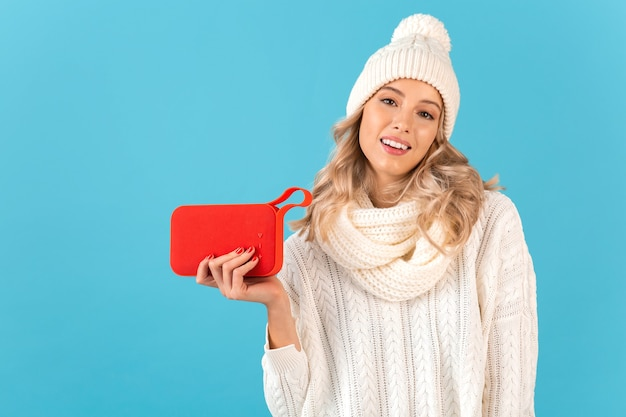 Stijlvolle blonde glimlachende mooie jonge vrouw met draadloze luidspreker die naar muziek luistert, gelukkig met witte trui en gebreide muts, winterse mode poseren
