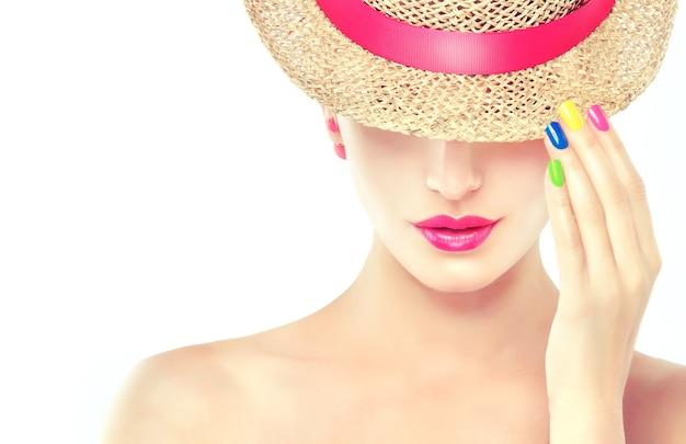 Stijlvolle blonde haired meisje gekleed in een strooien hoed met roze lint, toont trendy lichte make-up en veelkleurige nagellak op haar nagels. mode, manicure en cosmetica.