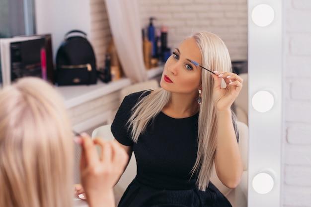 Stijlvolle blonde haren meisje in zwarte jurk haar wenkbrauwen borstelen kijken naar de spiegel in de schoonheidssalon