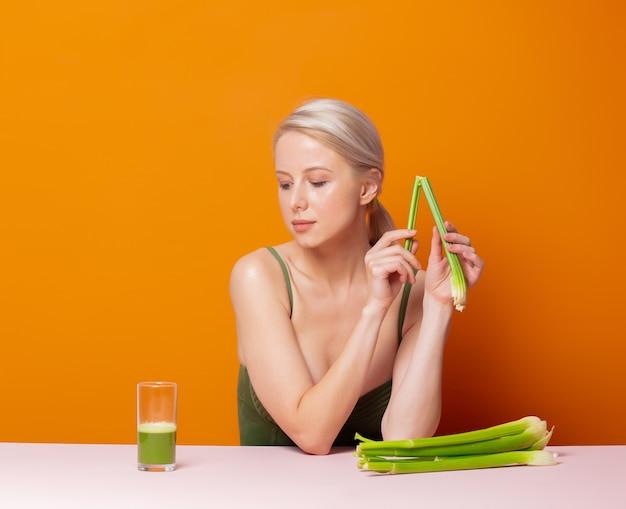 Stijlvolle blonde in een zwembroek zit aan de tafel naast selderijsap