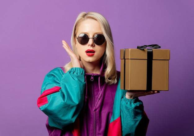 Stijlvolle blonde in windjack uit de jaren 80 en ronde zonnebril met geschenkdoos op paarse muur