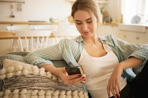 Stijlvolle blonde jonge vrouw zittend op de bank met slimme telefoon, vrienden online messaging. mooie vrouwelijke tiener nieuwsfeed via haar sociale media-account controleren, opmerkingen typen, foto's leuk vinden