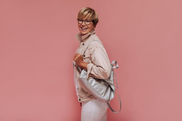 Stijlvolle blonde kortharige vrouw met bril in beige koel jasje en witte broek glimlachend en zak op roze achtergrond te houden.