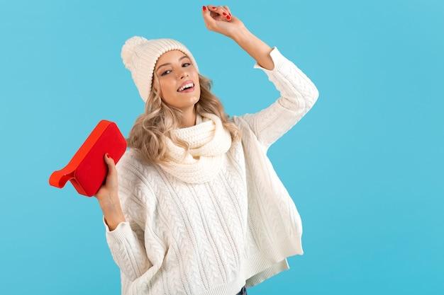 Stijlvolle blonde lachende mooie jonge vrouw met draadloze luidspreker luisteren naar muziek gelukkig dansen met witte trui en gebreide muts winter stijl mode poseren