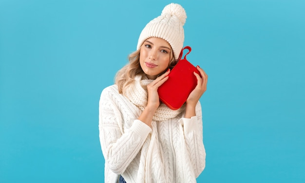 Stijlvolle blonde lachende mooie jonge vrouw met draadloze luidspreker luisteren naar muziek gelukkig dragen witte trui en gebreide muts winter stijl mode poseren geïsoleerd op blauwe achtergrond