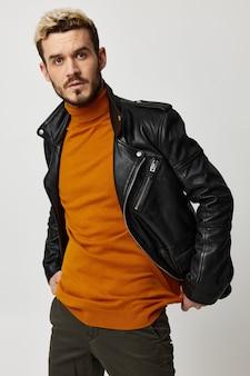 Stijlvolle blonde man in een trui en een leren jas op een lichte muur