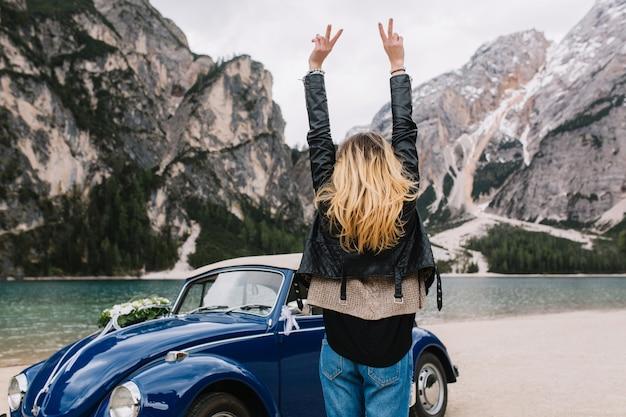 Stijlvolle blonde meisje dragen denim broek dansen buiten met handen omhoog in de buurt van blauwe klassieke auto