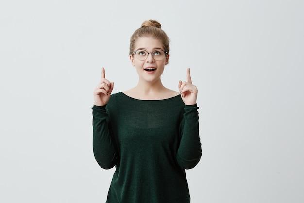 Stijlvolle blonde meisje met bril op, knalde ogen, steekt vingers op van opwinding, blij en verrast, heeft een goed humeur. mensen emoties en gevoelens. gezichtsuitdrukkingen