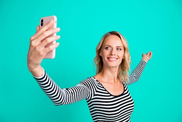 Stijlvolle blonde vrouw in een gestreepte trui poseren tegen de blauwe muur