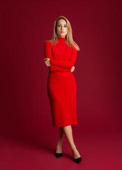 Stijlvolle blonde vrouw in het rode herfst winter mode jurk poseren geïsoleerd op rode muur