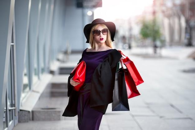 Stijlvolle blonde vrouw in zwarte jas, zonnebril en hoed met boodschappentassen wandelingen langs de straat, vakantieconcert
