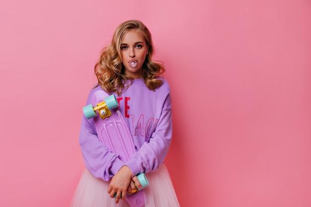 Stijlvolle blonde vrouw kauwgom bubble op roze maken. verveeld krullend meisje poseren met skateboard.