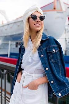 Stijlvolle blonde vrouw poseren door jachtclub buiten in zomer stad straat op zonsondergang tijd dragen witte korte broek en shirt met zwarte bril. vakantiestemming, reizen