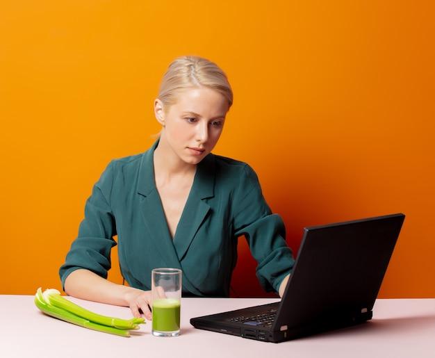 Stijlvolle blonde zit aan de tafel naast selderijsap en laptop