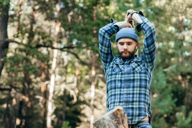 Stijlvolle boswachter die hout hakt met een bijl