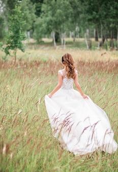 Stijlvolle bruid die met huwelijksboeket achteruitgaat op mooi landschap van overzees en bergen op zonsondergang