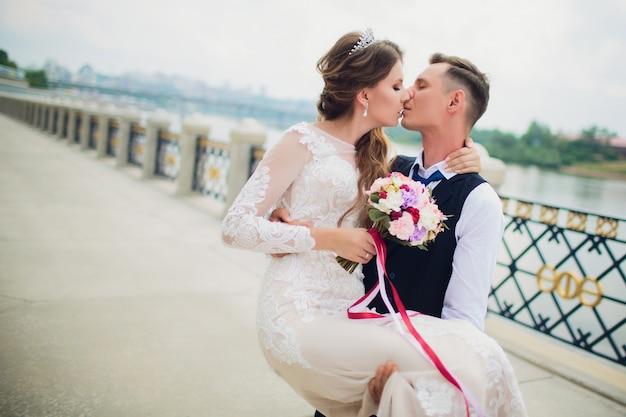 Stijlvolle bruid en bruidegom poseren op de achtergrond van de rivier.