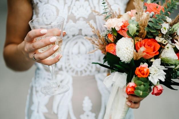 Stijlvolle bruid met bruiloft boeket bloemen en glas champagne in handen