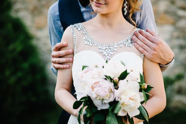 Stijlvolle bruid, vrouw met boeket van pioenrozen en bruidegom, man