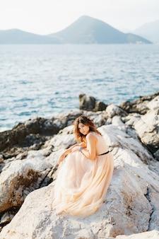 Stijlvolle bruid zit in een pastelkleurige trouwjurk op een klif boven de zee