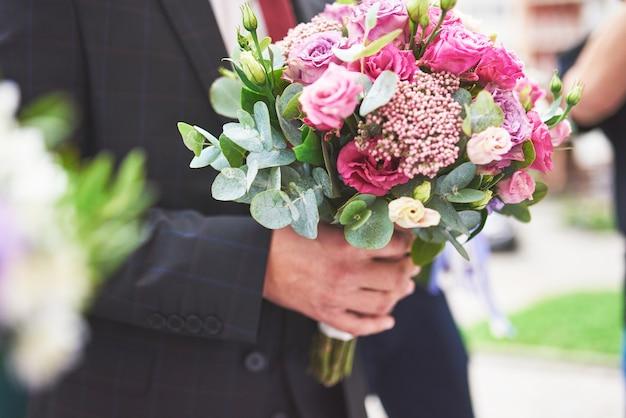 Stijlvolle bruidegom met een zacht roze bruiloft boeket.