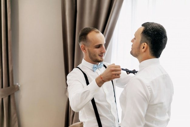 Stijlvolle bruidsjonkers die gelukkige bruidegom helpen die zich in de ochtend klaar maken voor huwelijksceremonie. luxe man in pak op kamer. ruimte voor tekst. trouwdag.