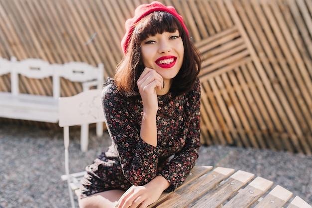 Stijlvolle brunette frans meisje in trendy rode baret met lichte make-up kwam naar terras voor de lunch. portret van elegante jonge vrouw in vintage kleding te wachten op haar bestelling in openluchtrestaurant.
