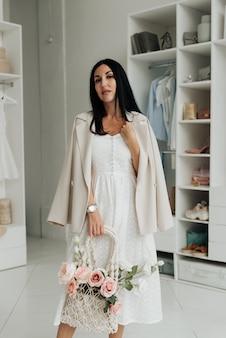 Stijlvolle brunette in een witte jurk en jasje met een mand met bloemen in de studio