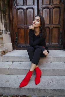Stijlvolle brunette meisje, zittend op de trap