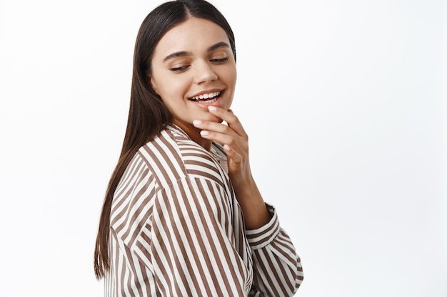 Stijlvolle brunette vrouw die haar lippen aanraakt en glimlacht, neerkijkt met een koket en flirterig gezicht, staande tegen een witte muur