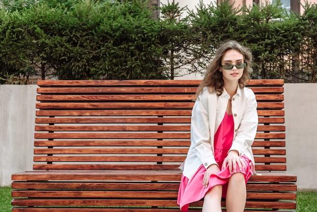 Stijlvolle brunette vrouw in glazen positioner zittend op een bankje in een nieuwe collectie kleding kijkend naar de camera