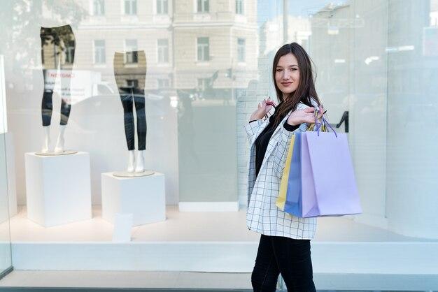 Stijlvolle brunette vrouw met veelkleurige boodschappentassen op showcase achtergrond. bespotten.