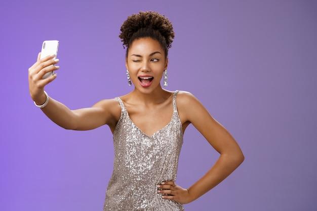 Stijlvolle brutaal afro-amerikaanse b-day meisje selfie nieuwe elegante zilveren glanzende jurk uitstrekken arm houden smartphone poseren knipogend scherm geamuseerd plezier glimlachend breed, blauwe achtergrond.