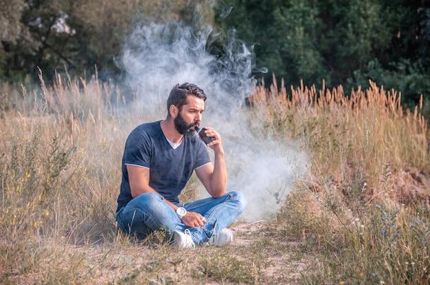 Stijlvolle brutale man blaast veel rook met behulp van elektronische vape rookapparaat
