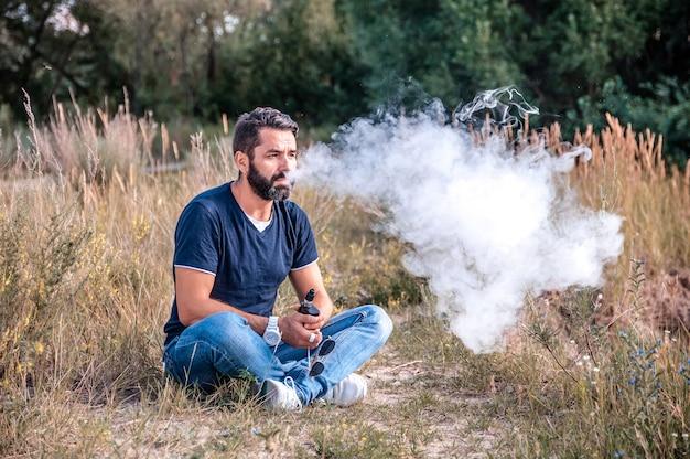Stijlvolle brute man houdt vast en rookt zijn elektronische sigaret die een stroom rook verspreidt.