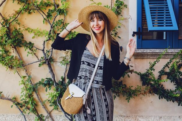 Stijlvolle casual elegante vrouw in strooien hoed en zwarte jas poseren op straat
