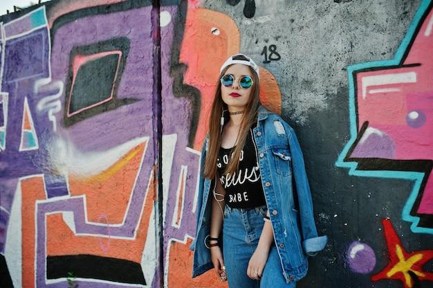 Stijlvolle casual hipster meisje in pet, zonnebril en jeans dragen, tegen grote graffiti muur.