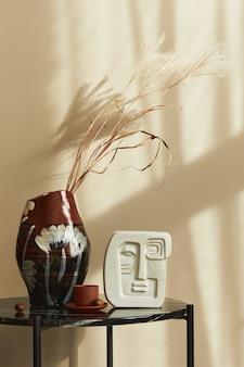 Stijlvolle compositie bij chique interieur met marmeren salontafel, gedroogde bloem in vaas en kopje koffie in modern interieur. details.