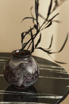 Stijlvolle compositie bij chique interieur met marmeren salontafel, gedroogde zwarte bloem in vaas in modern interieur. details. sjabloon.