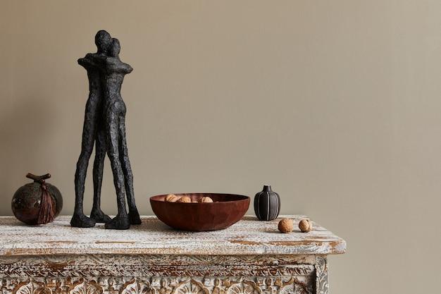 Stijlvolle compositie bij marokkaans interieur met houten plank, koppelfiguur, houten kom met noten en decoratie in modern huisdecor. details... kopieer de ruimte.