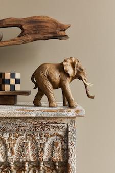 Stijlvolle compositie bij marokkaans interieur met houten plank, kubus, design olifant figuur en decoratie in modern interieur. details.